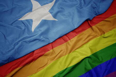 waving colorful rainbow flag and national flag of somalia. macro