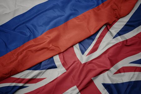 waving colorful flag of great britain and national flag of russia. macro