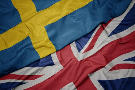 waving colorful flag of great britain and national flag of sweden. macro