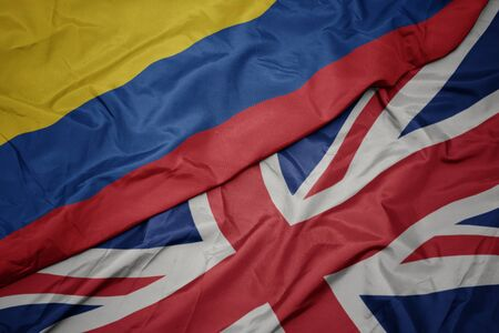 waving colorful flag of great britain and national flag of colombia. macro