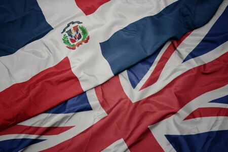 waving colorful flag of great britain and national flag of dominican republic. macro Фото со стока