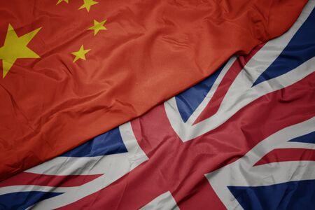 brandissant le drapeau coloré de la grande-bretagne et le drapeau national de la chine. macro