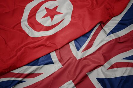 waving colorful flag of great britain and national flag of tunisia. macro