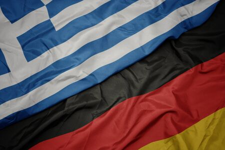 waving colorful flag of germany and national flag of greece. macro Standard-Bild