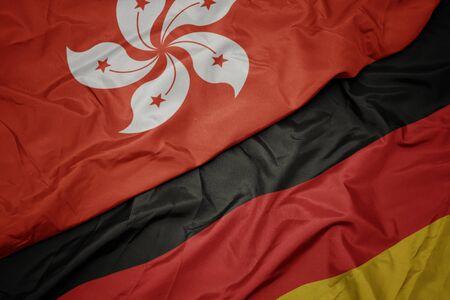 waving colorful flag of germany and national flag of hong kong. macro
