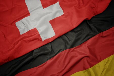 waving colorful flag of germany and national flag of switzerland. macro