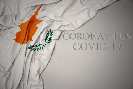 waving colorful national flag of cyprus on a gray background with text coronavirus covid-19 . concept.