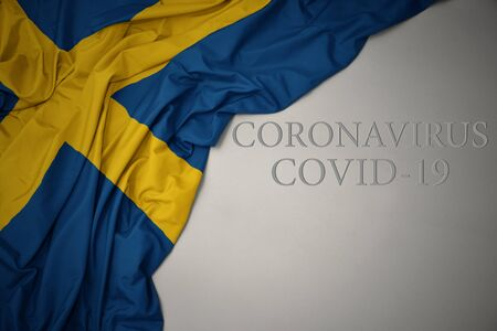 waving colorful national flag of sweden on a gray background with text coronavirus covid-19 . concept.
