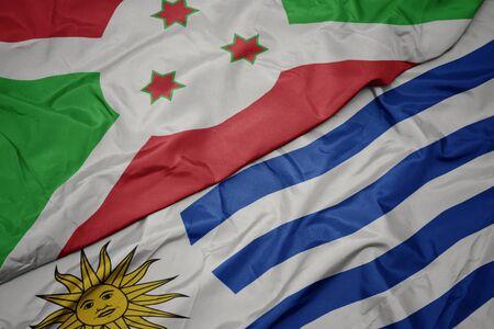 waving colorful flag of uruguay and national flag of burundi . macro