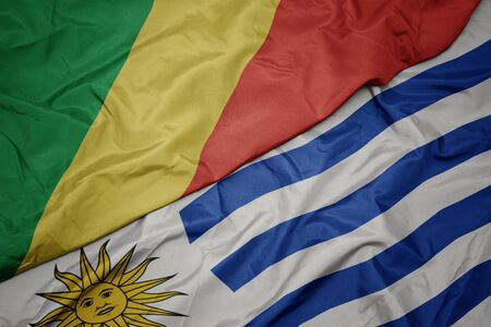 waving colorful flag of uruguay and national flag of republic of the congo. macro Stock Photo