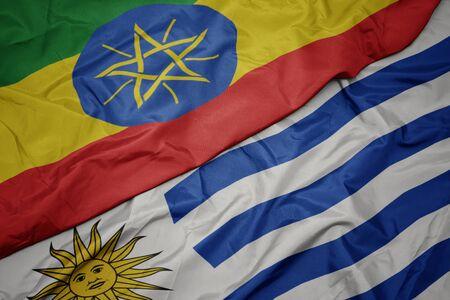 waving colorful flag of uruguay and national flag of ethiopia . macro
