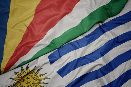 waving colorful flag of uruguay and national flag of seychelles. macro Stock Photo