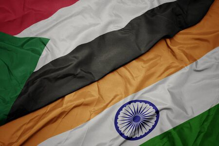 waving colorful flag of india and national flag of sudan. macro