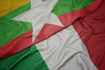 waving colorful flag of italy and national flag of myanmar. macro