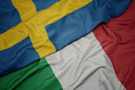 waving colorful flag of italy and national flag of sweden. macro