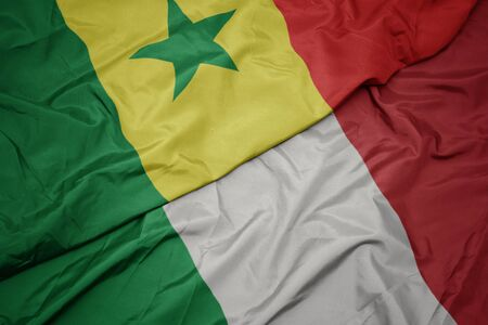 waving colorful flag of italy and national flag of senegal. macro