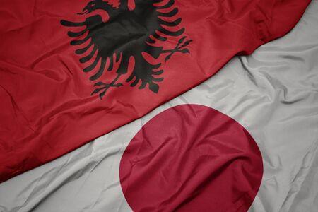 waving colorful flag of japan and national flag of albania. macro
