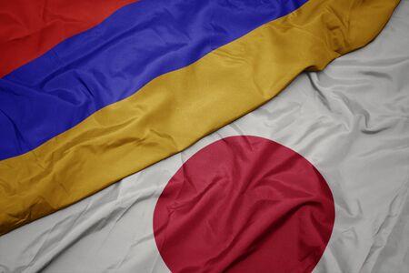 waving colorful flag of japan and national flag of armenia. macro