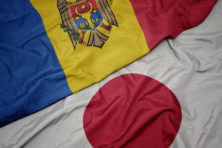 waving colorful flag of japan and national flag of moldova. macro 写真素材
