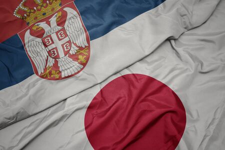 waving colorful flag of japan and national flag of serbia. macro