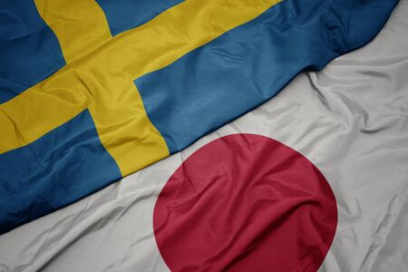 waving colorful flag of japan and national flag of sweden. macro