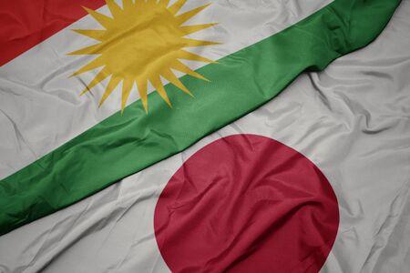 waving colorful flag of japan and national flag of kurdistan. macro 写真素材