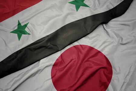 waving colorful flag of japan and national flag of syria. macro