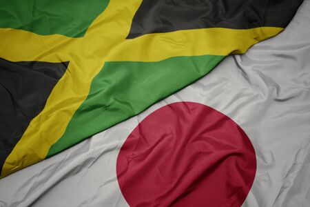 waving colorful flag of japan and national flag of jamaica. macro 写真素材