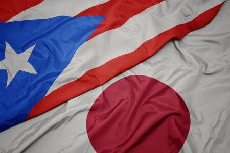 waving colorful flag of japan and national flag of puerto rico. macro