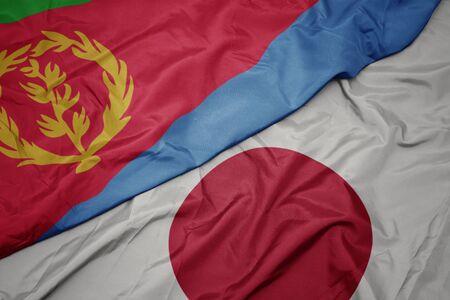 waving colorful flag of japan and national flag of eritrea. macro 写真素材