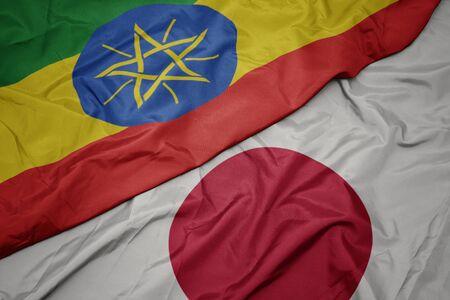 waving colorful flag of japan and national flag of ethiopia. macro 写真素材