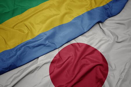 waving colorful flag of japan and national flag of gabon. macro