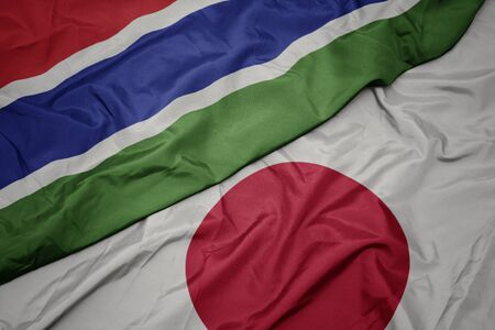 waving colorful flag of japan and national flag of gambia. macro