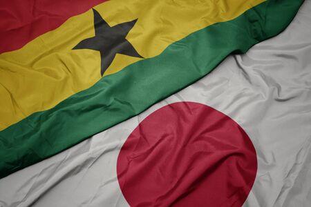 waving colorful flag of japan and national flag of ghana. macro