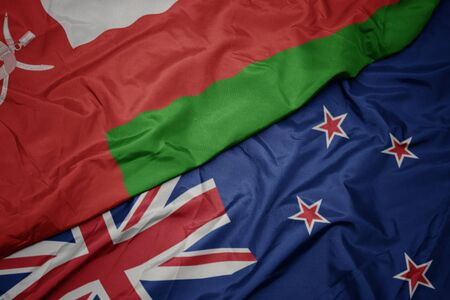 waving colorful flag of new zealand and national flag of oman. macro