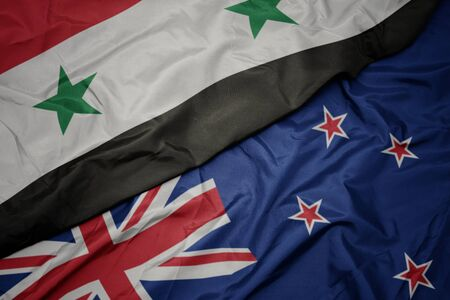 waving colorful flag of new zealand and national flag of syria. macro