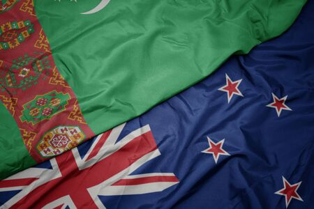 waving colorful flag of new zealand and national flag of turkmenistan. macro 写真素材