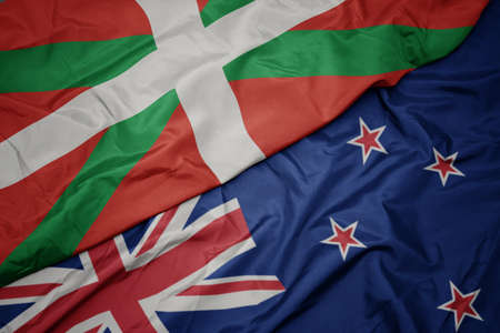 waving colorful flag of new zealand and national flag of basque country. macro