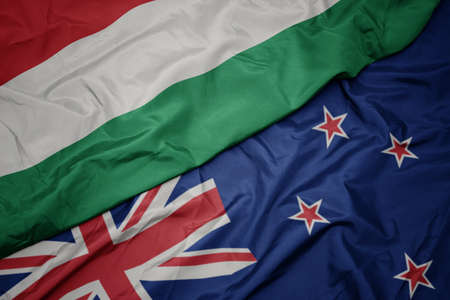 waving colorful flag of new zealand and national flag of hungary. macro
