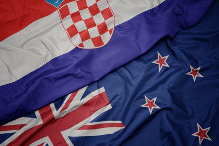 waving colorful flag of new zealand and national flag of croatia. macro