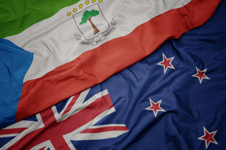 waving colorful flag of new zealand and national flag of equatorial guinea. macro