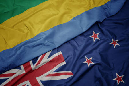 waving colorful flag of new zealand and national flag of gabon. macro