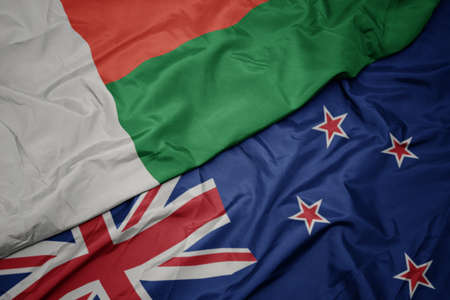 waving colorful flag of new zealand and national flag of madagascar. macro