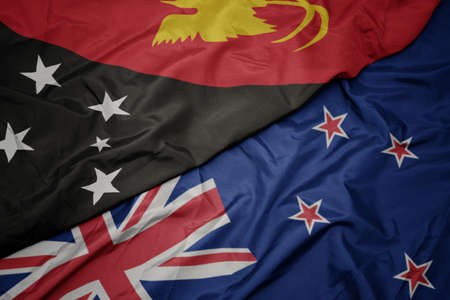 waving colorful flag of new zealand and national flag of Papua New Guinea. macro