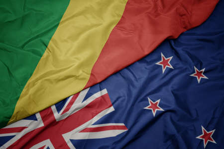 waving colorful flag of new zealand and national flag of republic of the congo. macro