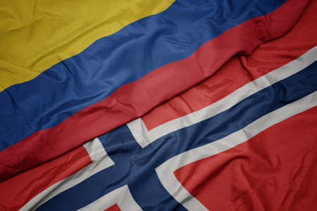 waving colorful flag of norway and national flag of colombia. macro