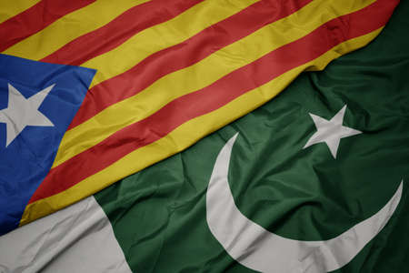 waving colorful flag of pakistan and national flag of catalonia. macro