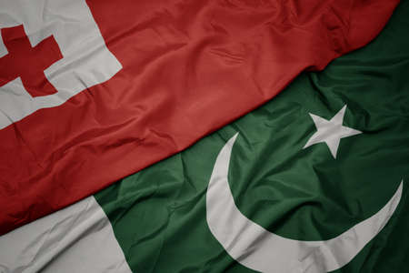 waving colorful flag of pakistan and national flag of Tonga , . macro