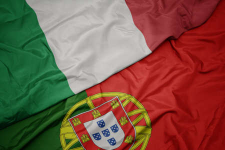 waving colorful flag of portugal and national flag of italy. macro