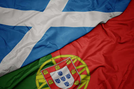 waving colorful flag of portugal and national flag of scotland. macro